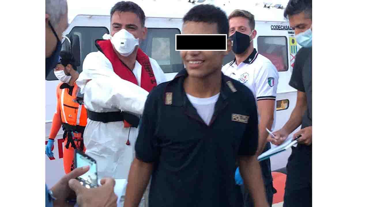 Giovane migrante sbarca a Lampedusa indossando una maglia della Polizia di Stato